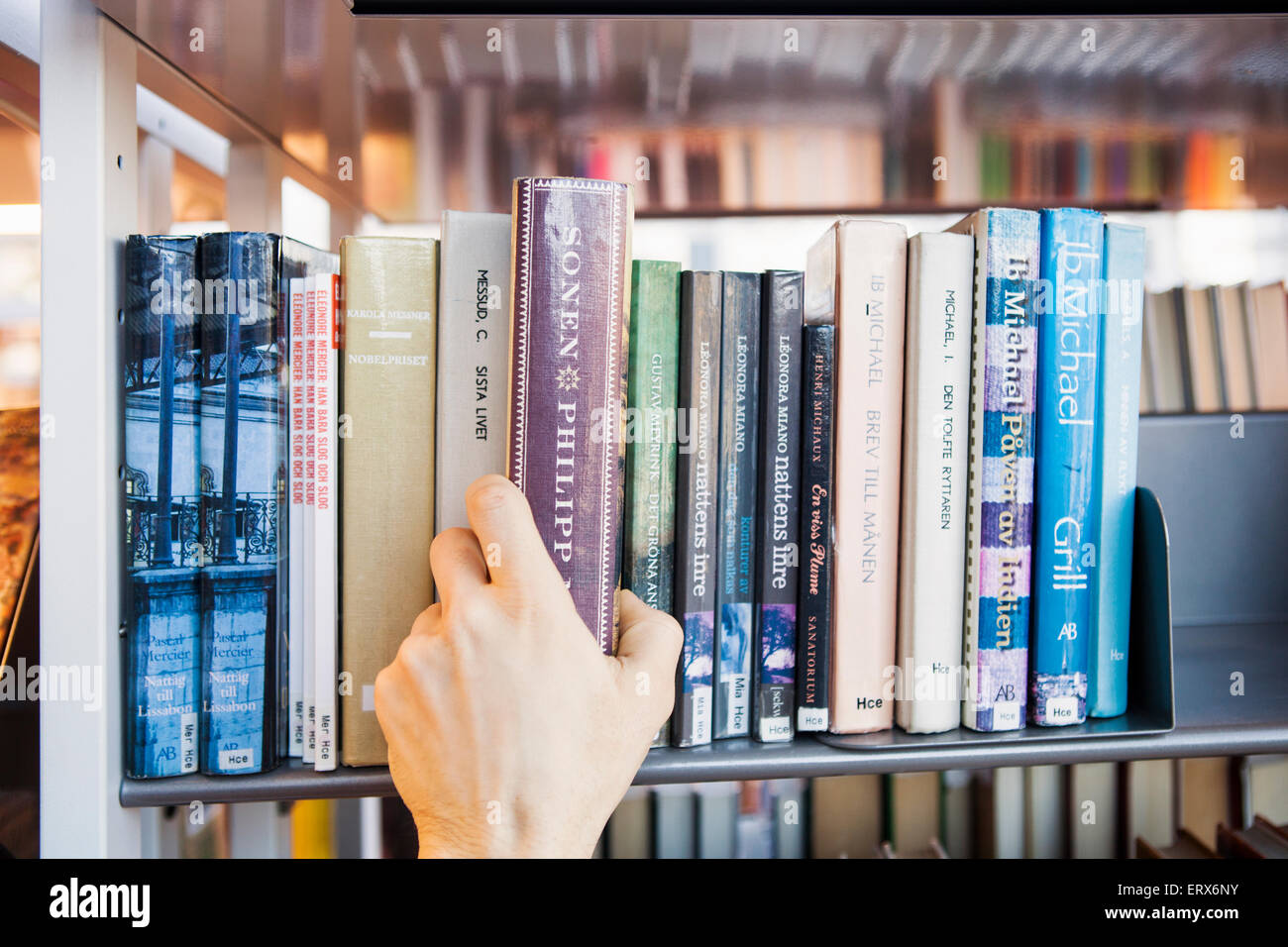 Cropped image of man's hand choosing book from shelf in library - Stock Image