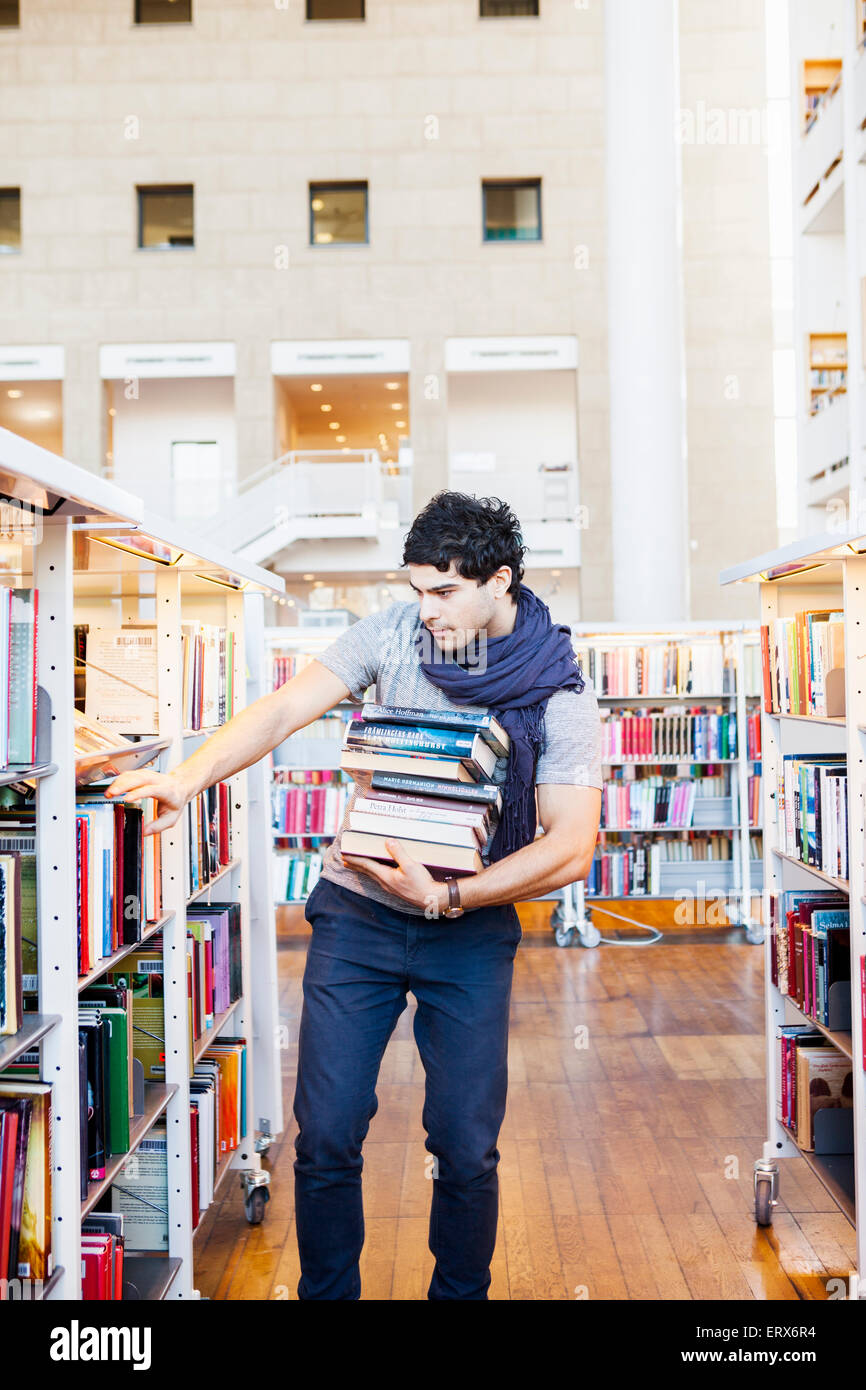 Young man in casuals selecting books in library - Stock Image
