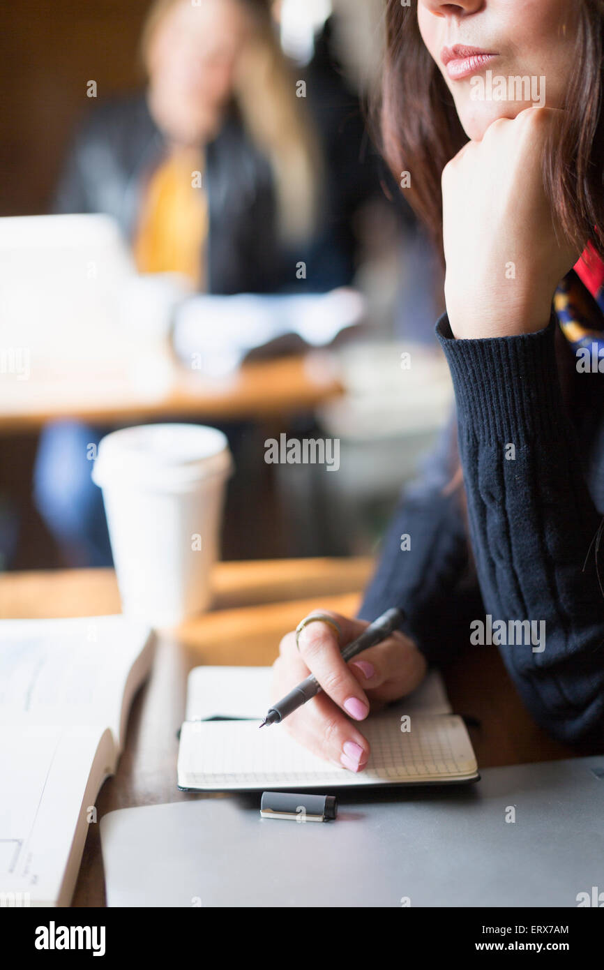 Cropped image of young woman with diary and pen at table in cafe - Stock Image