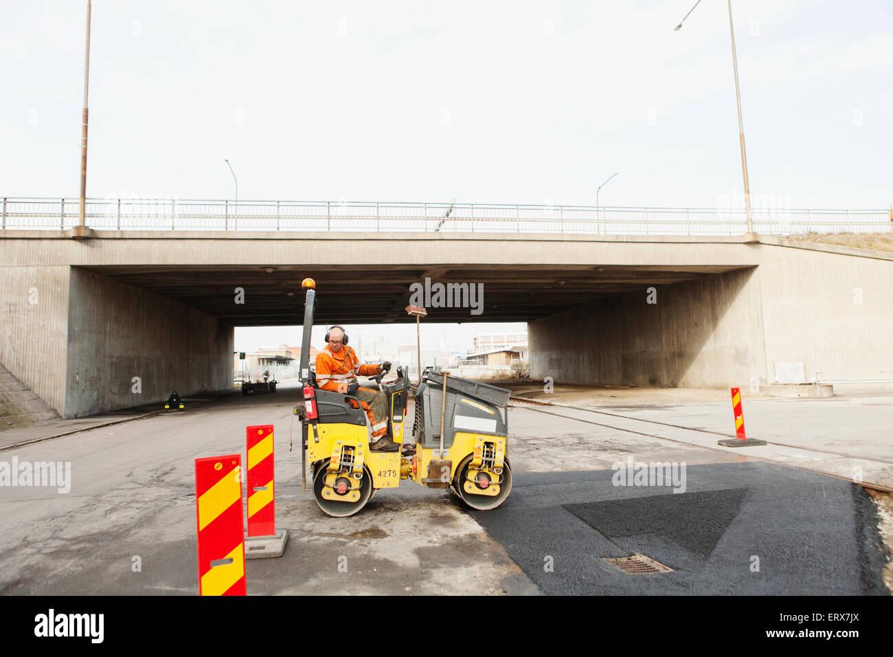 Manual worker driving steamroller on tar by bridge - Stock Image