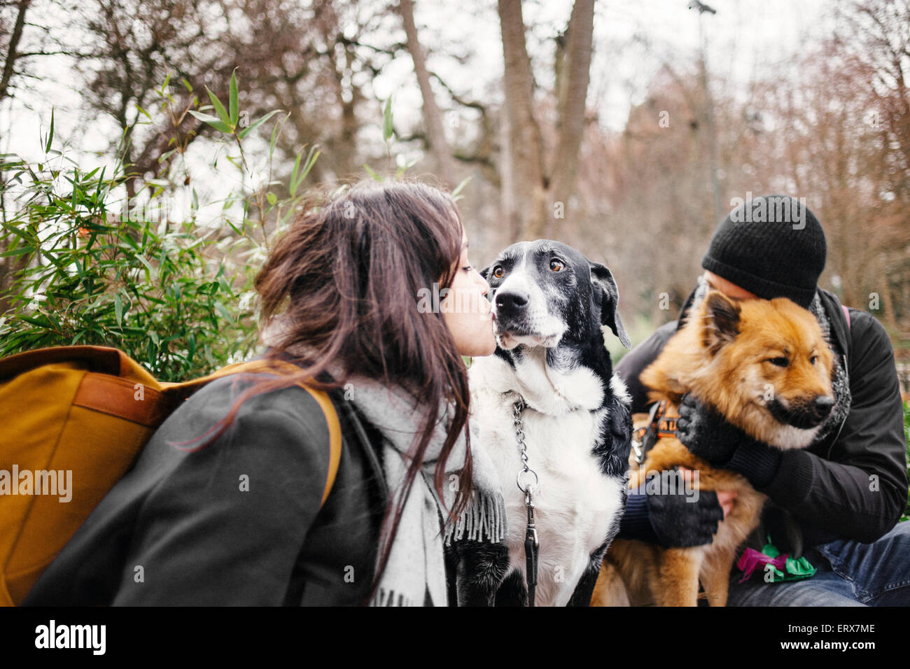 Loving young couple with dogs at park - Stock Image