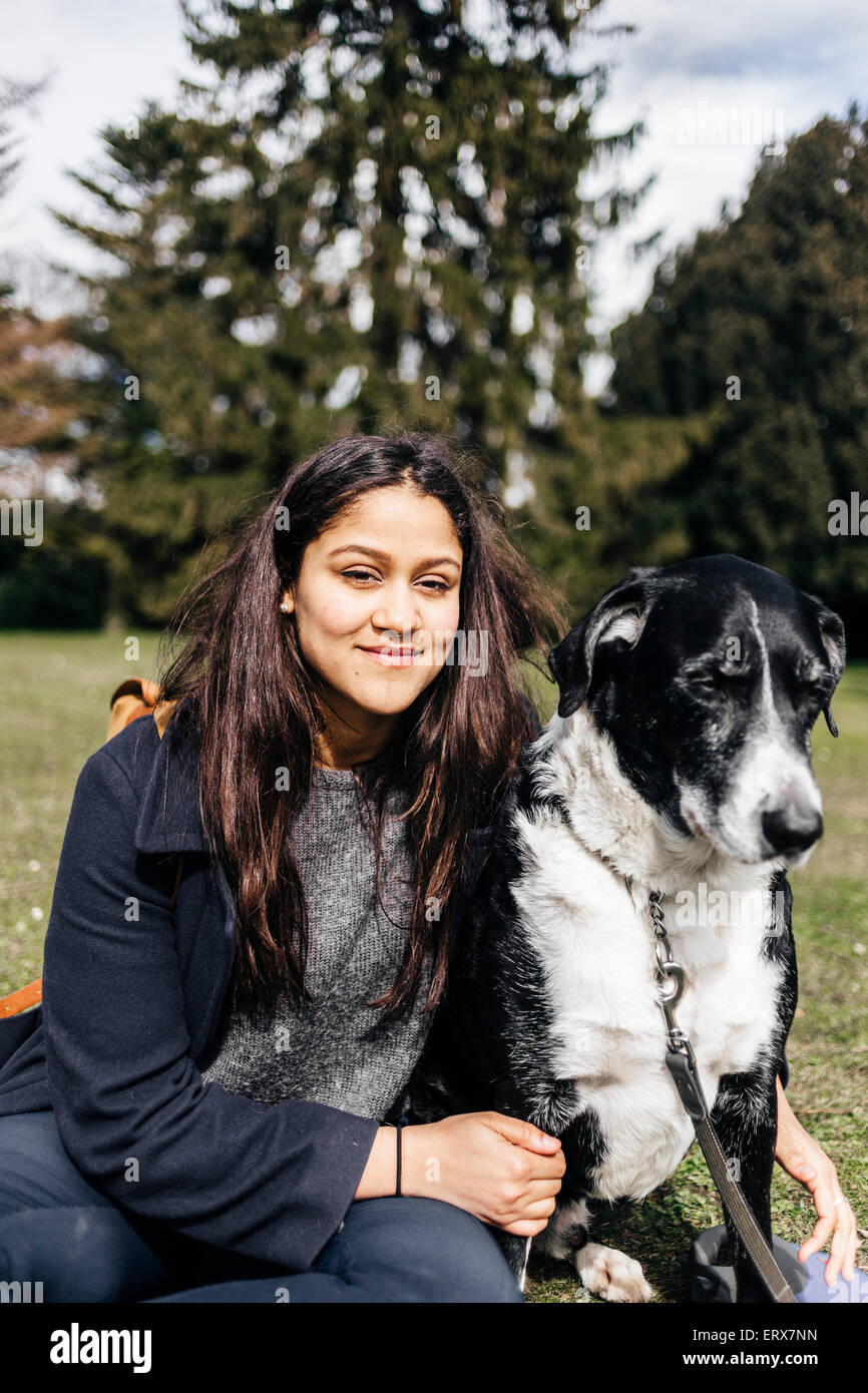 Portrait of smiling woman sitting with mixed-breed dog at park - Stock Image