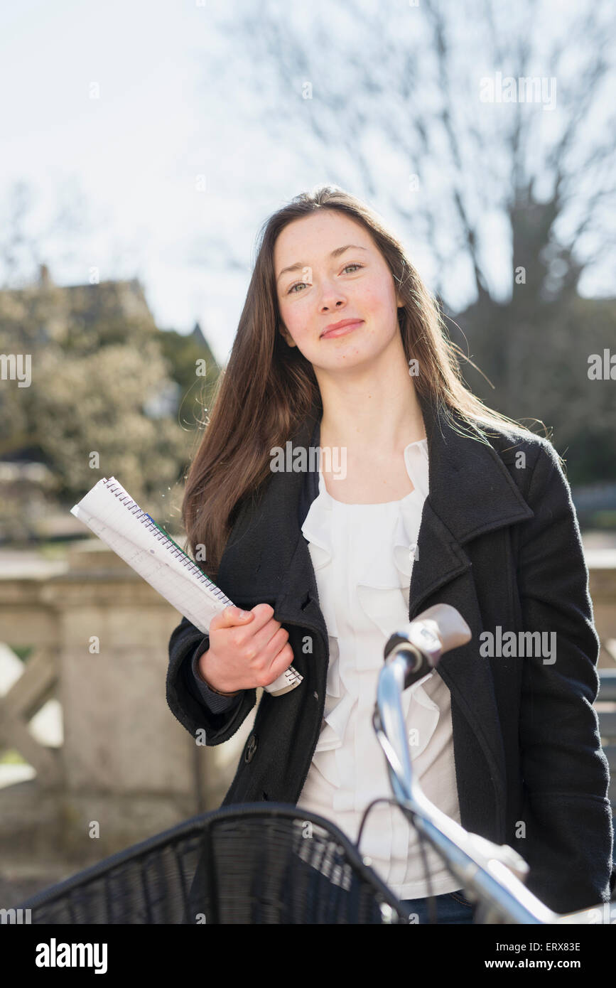Portrait of beautiful teenage girl with book outdoors - Stock Image