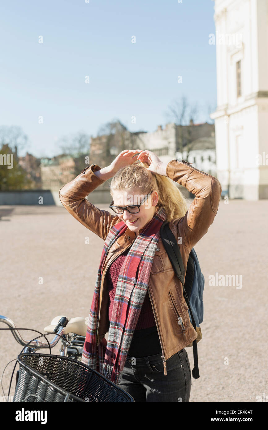 Happy teenage girl with bicycle tying up hair in college campus - Stock Image