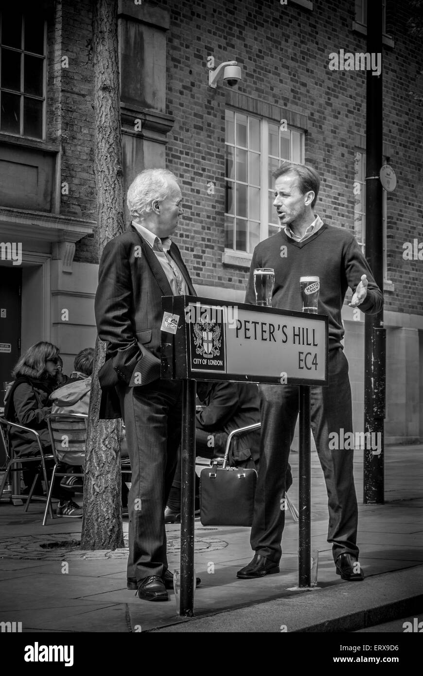 Two men having a lunchtime drink and chat outside, Peter's Hill, London, UK. - Stock Image
