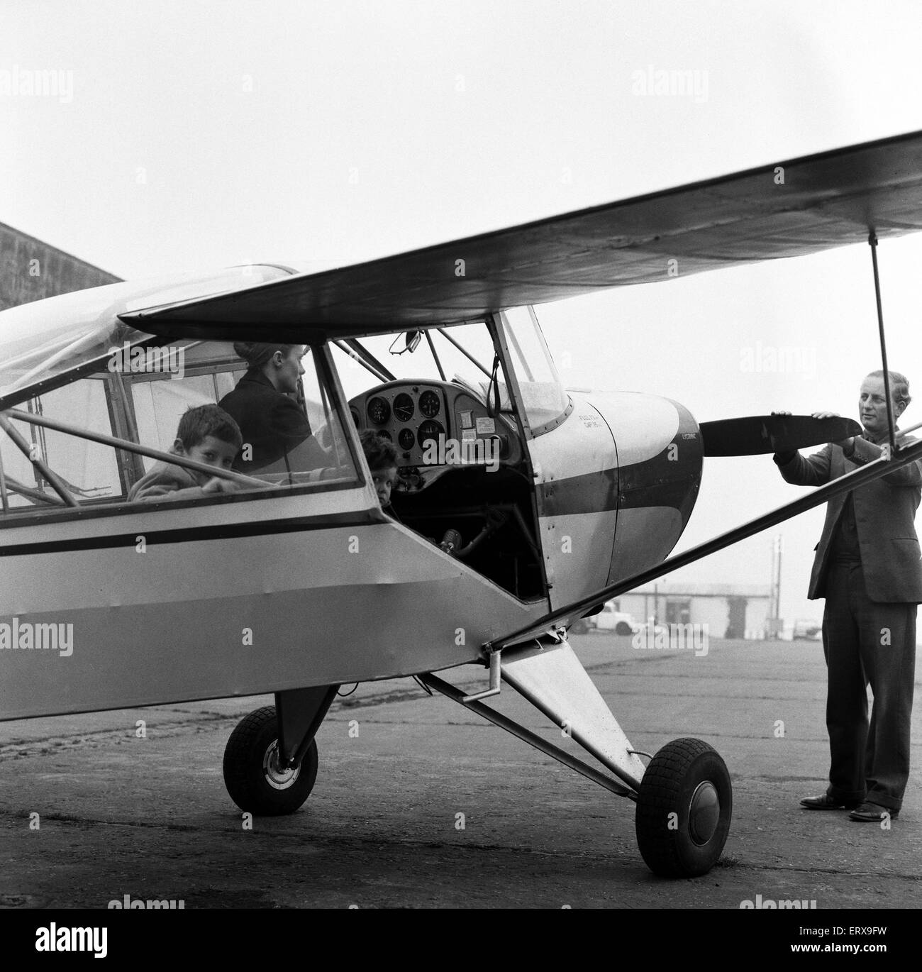 Mrs Diana Freeman from Headcorn, Kent explains the controls of her Auster aircraft wile her children Jamie, aged - Stock Image