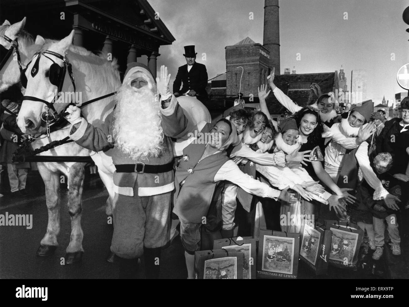 Father Christmas accompanied by Snow White and the seven dwarfs, a pantomime horse, Aladdin, and other colourful - Stock Image