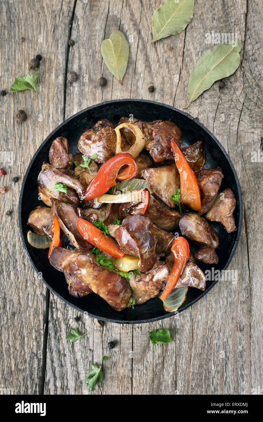 Grilled chicken liver with red pepper in frying pan on wooden table, top view Stock Photo
