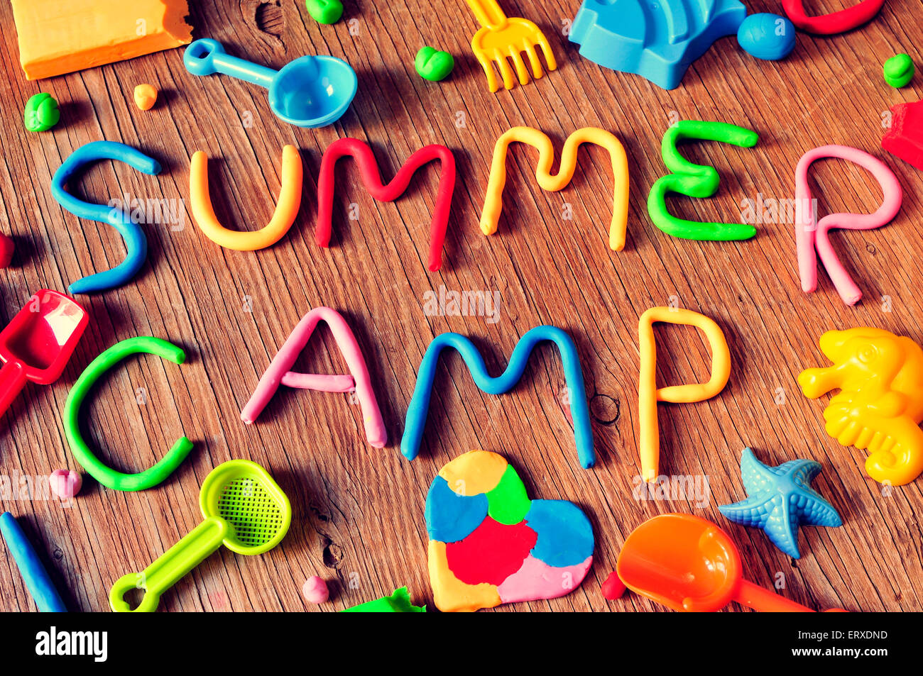 the text summer camp made from modelling clay of different colors and some beach toys such as toy shovels and sand - Stock Image