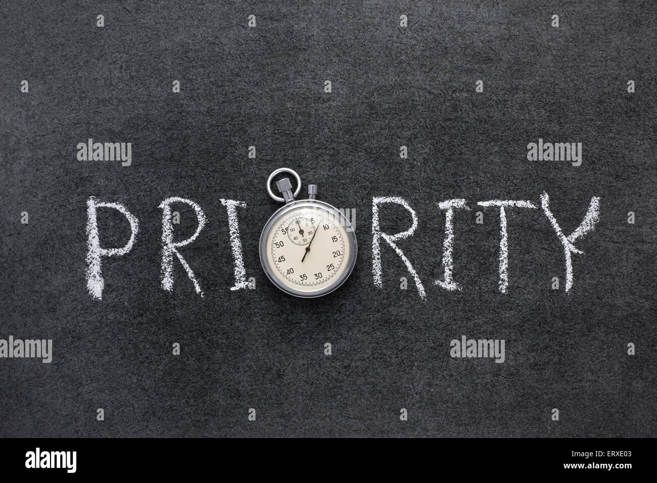 priority word handwritten on chalkboard with vintage precise stopwatch used instead of O - Stock Image