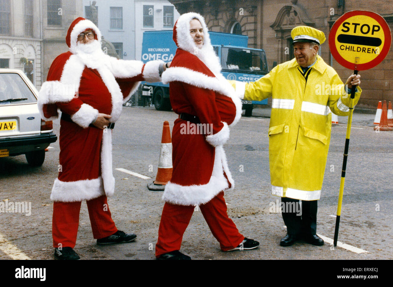 Stirling's slimming Santa's Robert Grant (wearing glasses) and Peter Hawkins get a helping hand to cross - Stock Image