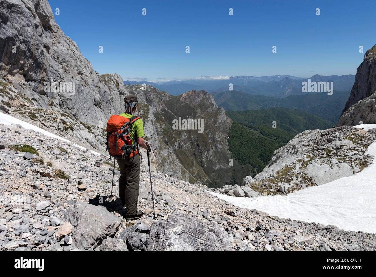 Hiker in the Collado de Liordes with the Decent Path of the Canal del Embudo Below, Fuenta De, Picos de Europa Mountains, - Stock Image