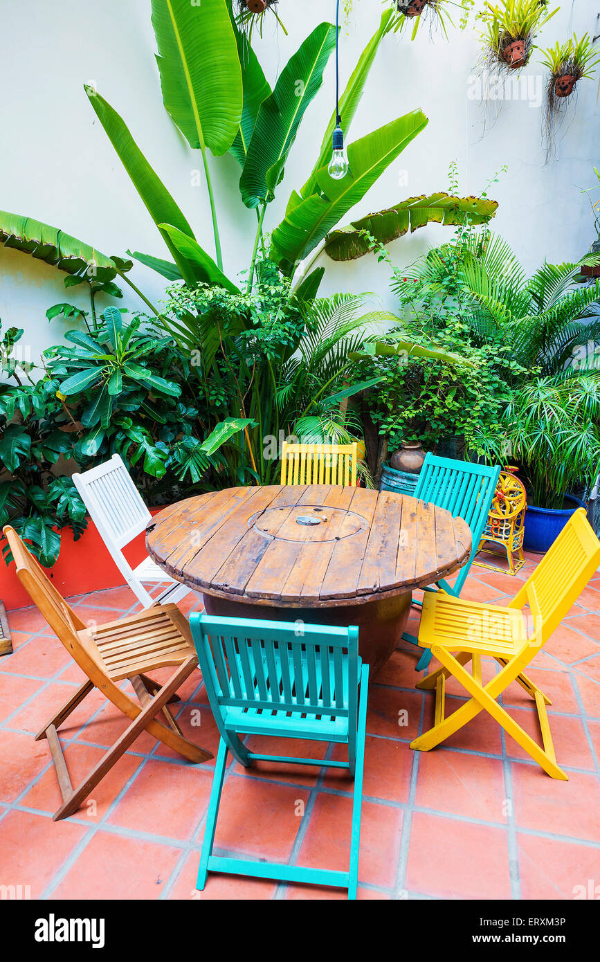 brightly coloured funky wooden chairs and table in garden Stock