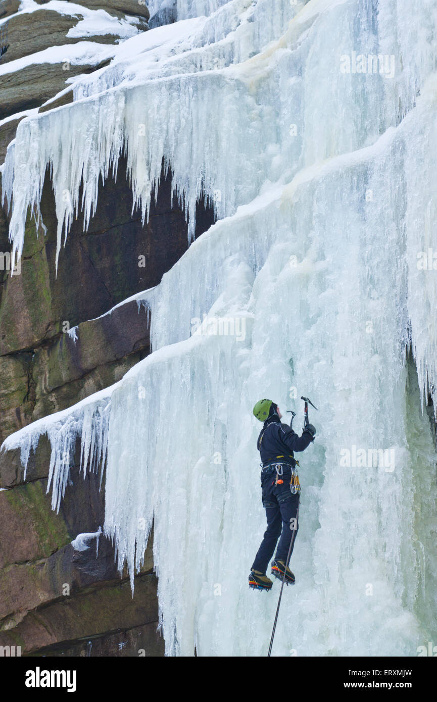 Ice climber climbing a frozen waterfall Kinder Downfall on Kinder Scout Derbyshire Peak district England UK GB EU - Stock Image