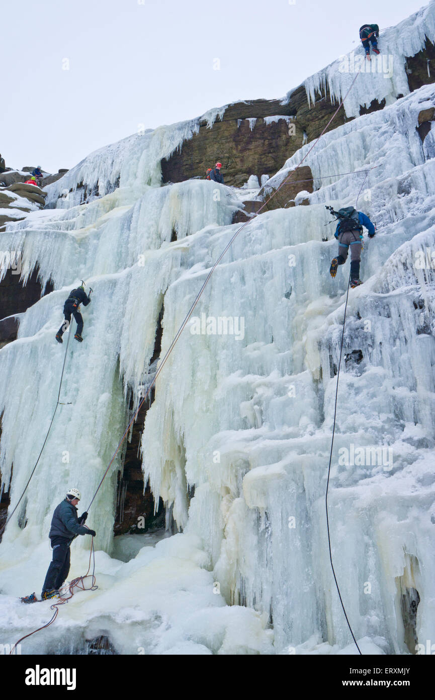 Ice climbers climbing a frozen waterfall Kinder Downfall on Kinder Scout Derbyshire Peak district England UK GB - Stock Image