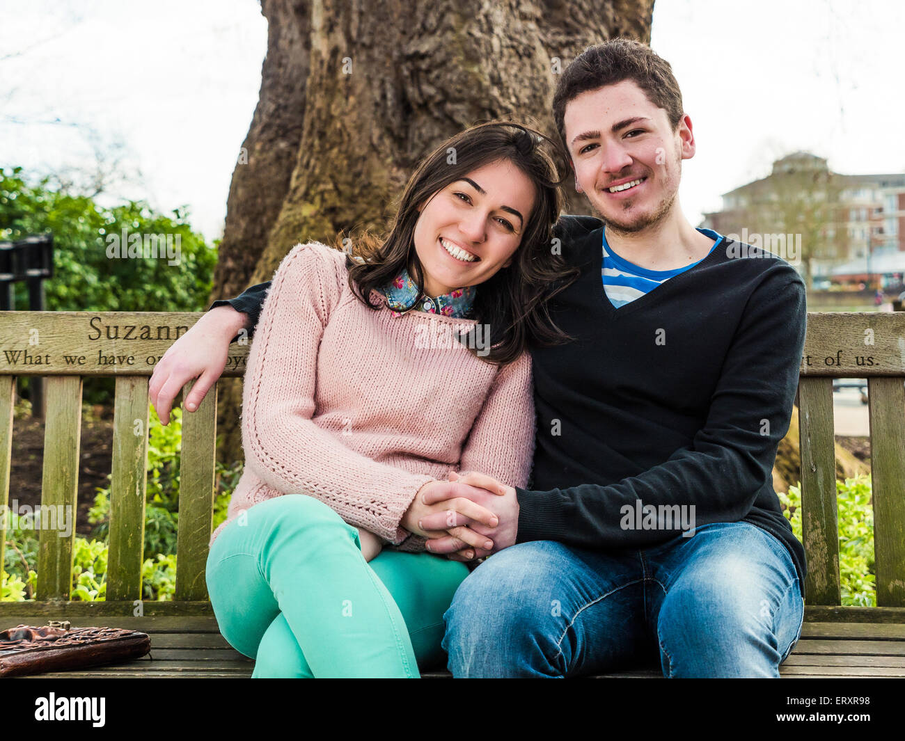 Young Heterosexual Couple Sitting on a Park Bench Enjoying a Beautiful Sunny Day and Smiling Looking at the Camera - Stock Image