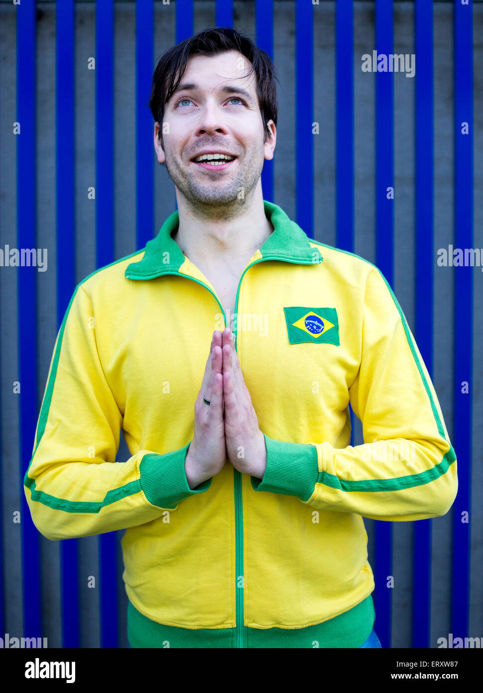man in yellow trikot is looking up the sky and praying with a smile - Stock Image
