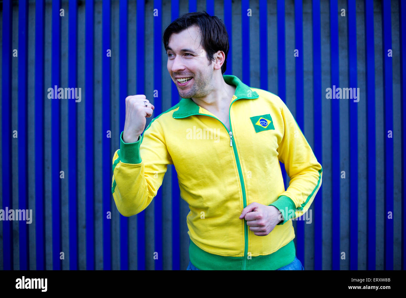 man in yellow sports trikot makes a fist for victory - Stock Image