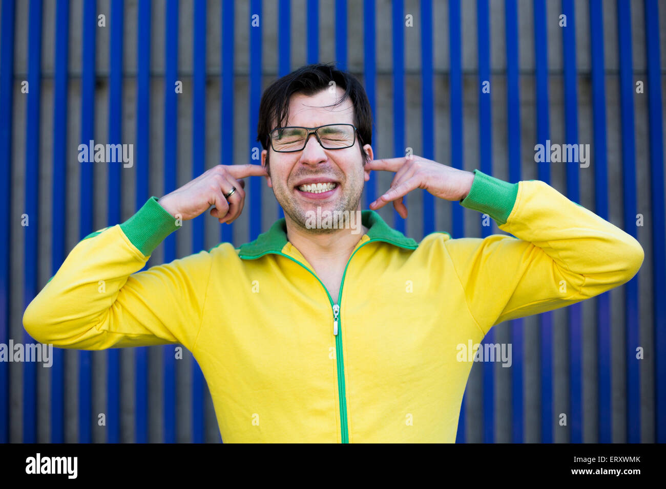 man in yellow trikot shuts his ears with his fingers and has his eyes closed - Stock Image