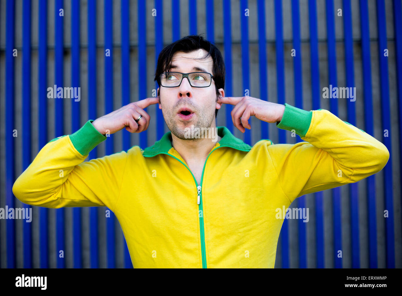 man in yellow trikot shuts his ears with his fingers and pretends not to hear anything - Stock Image