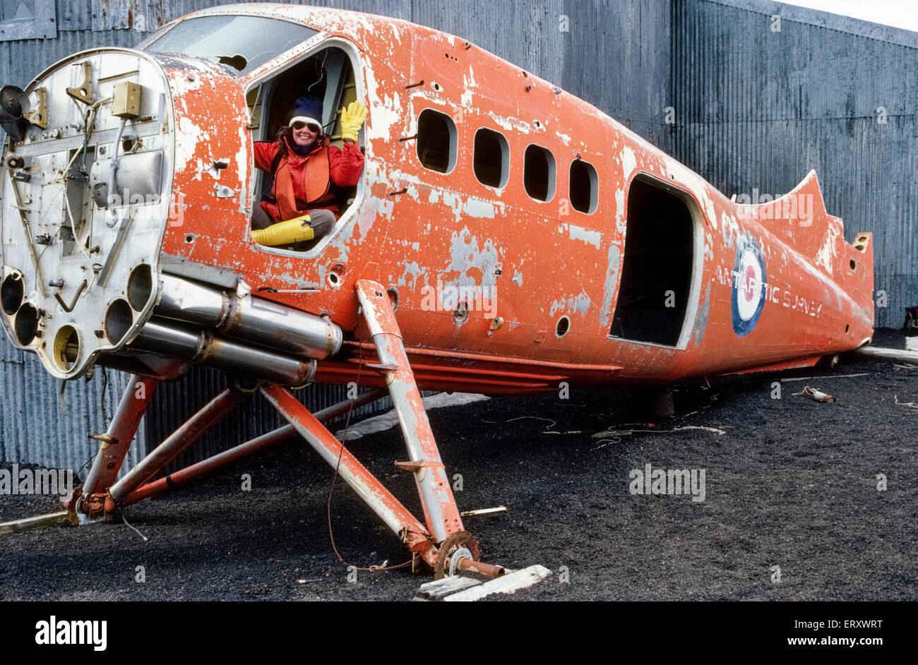 A visitor to Antarctica waves from a de Havilland Otter aircraft once used for the British Antarctic Survey that - Stock Image