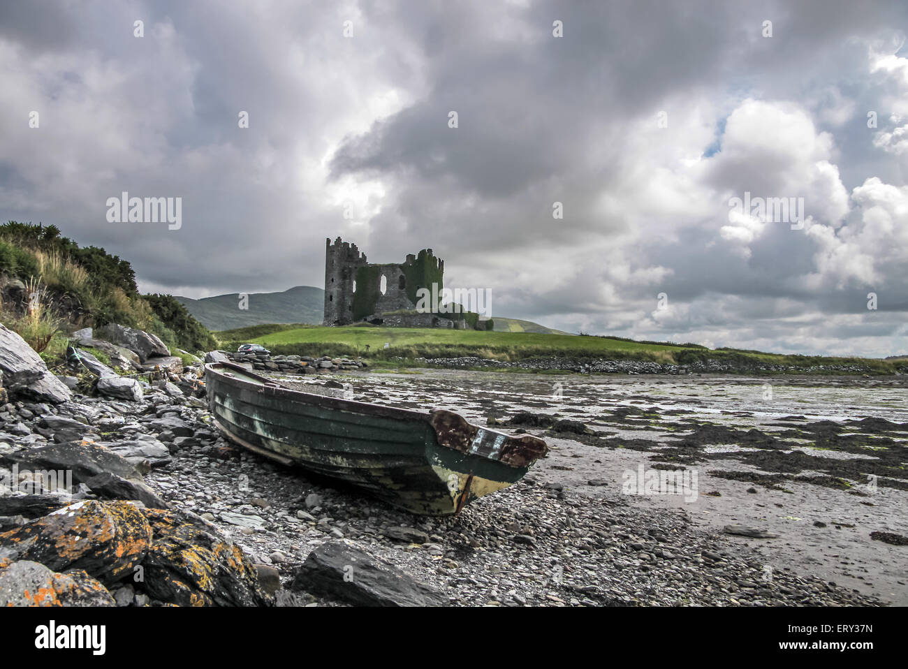 Ballycarbery Castle with old boat on the Ring of Kerry in Cahersiveen, County Kerry, Ireland - Stock Image