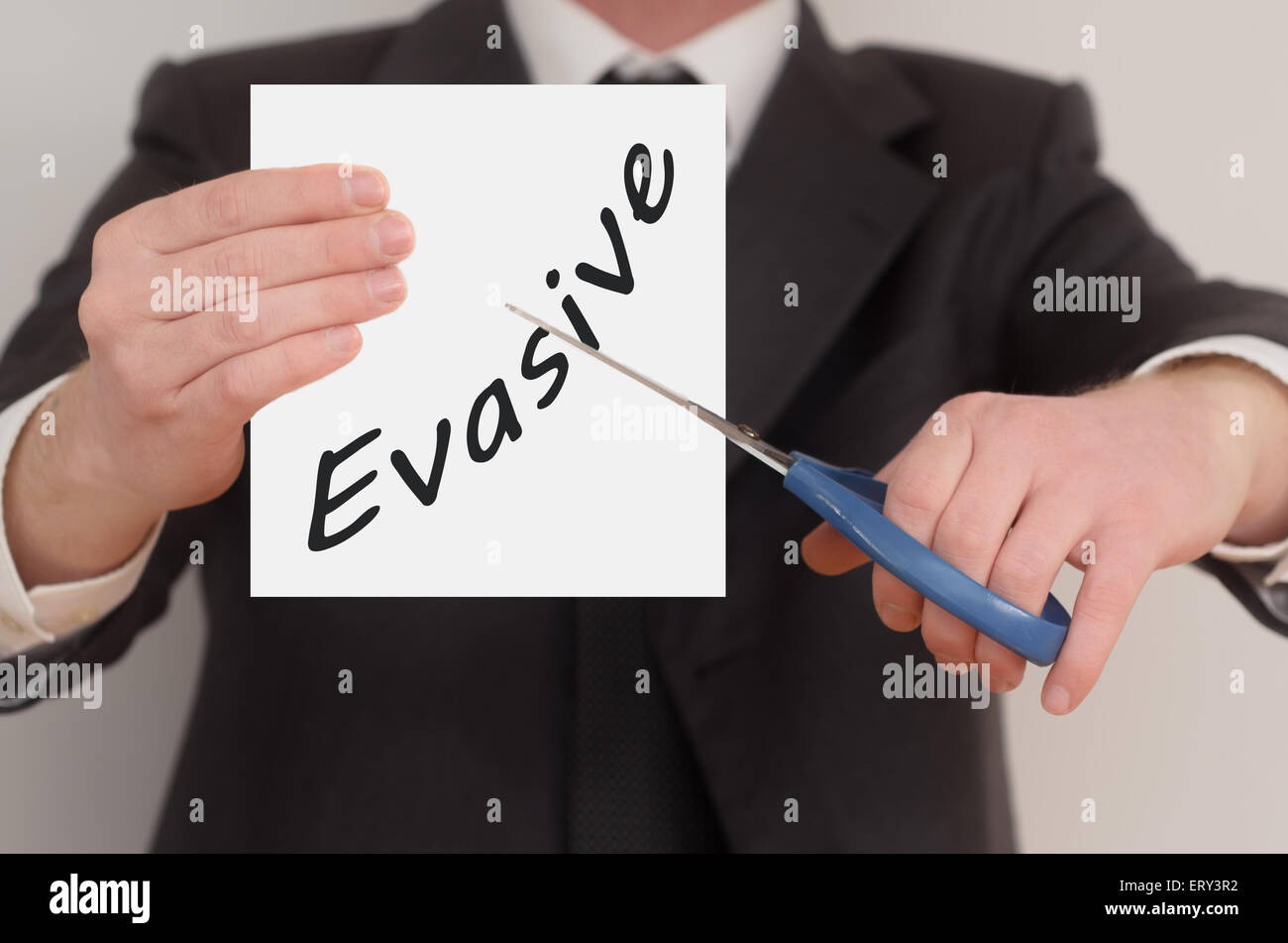 Evasive, man in suit cutting text on paper with scissors - Stock Image