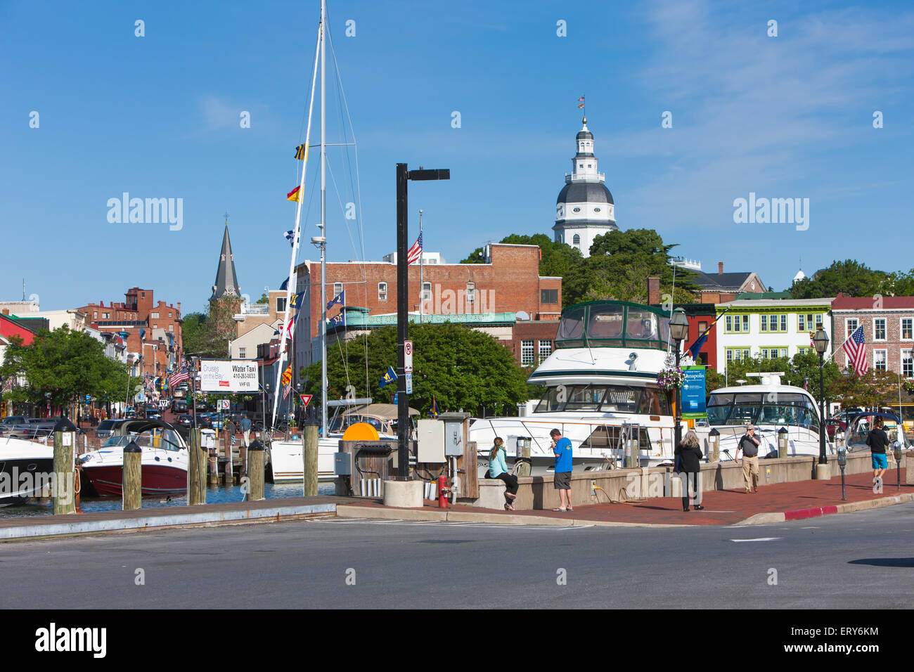 Yachts and sailboats are docked in slips in the Annapolis City Dock on Spa Creek, with Main Street and the Capitol - Stock Image