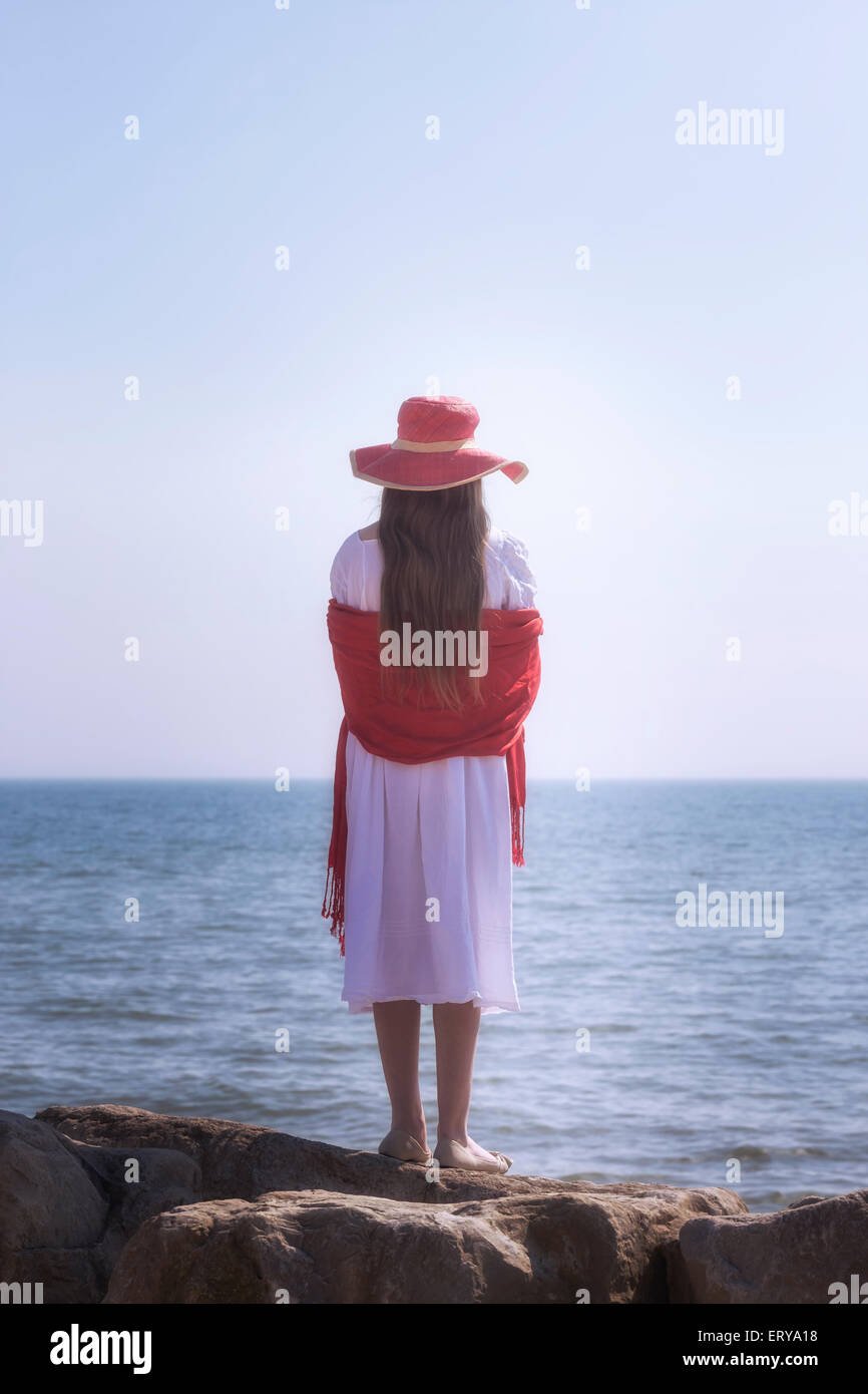 a girl in a white dress with red sunhat and shawl is standing on rocks at the sea - Stock Image