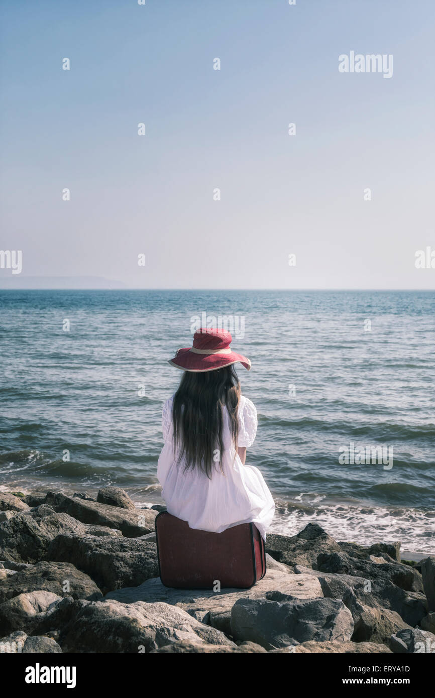 a girl in a white dress with a red sunhat is sitting on a suitcase at the sea - Stock Image