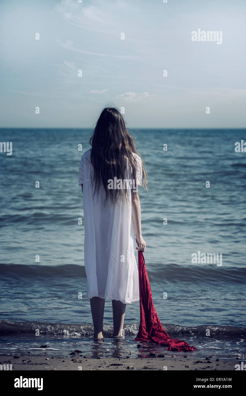 a girl in a white dress is standing on a beach with a red scarf - Stock Image