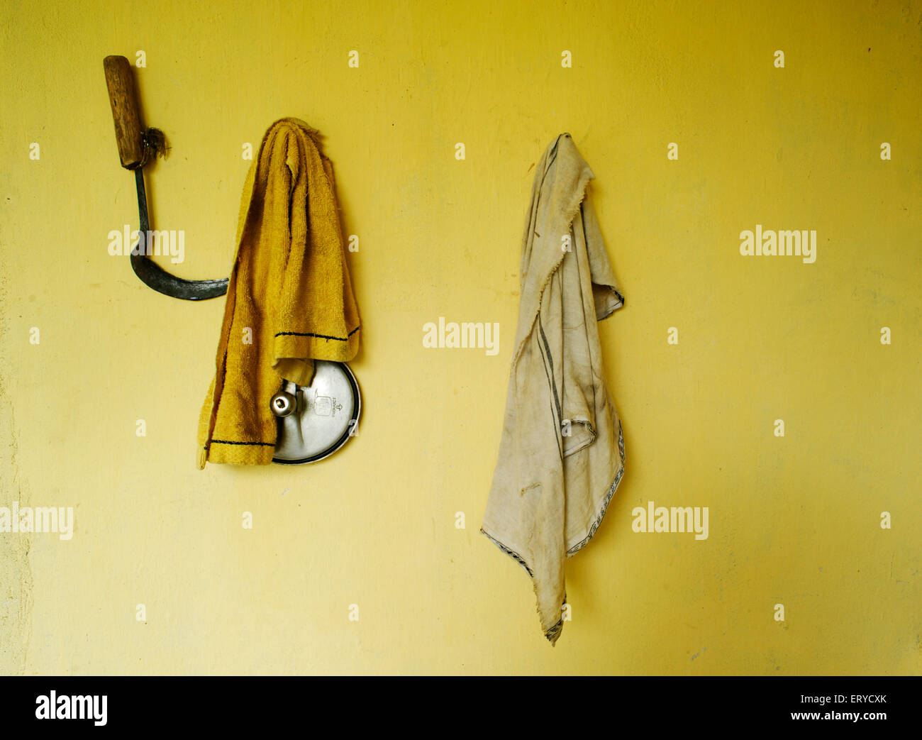Sickle and clothes hanging on peg ; Nepal - Stock Image