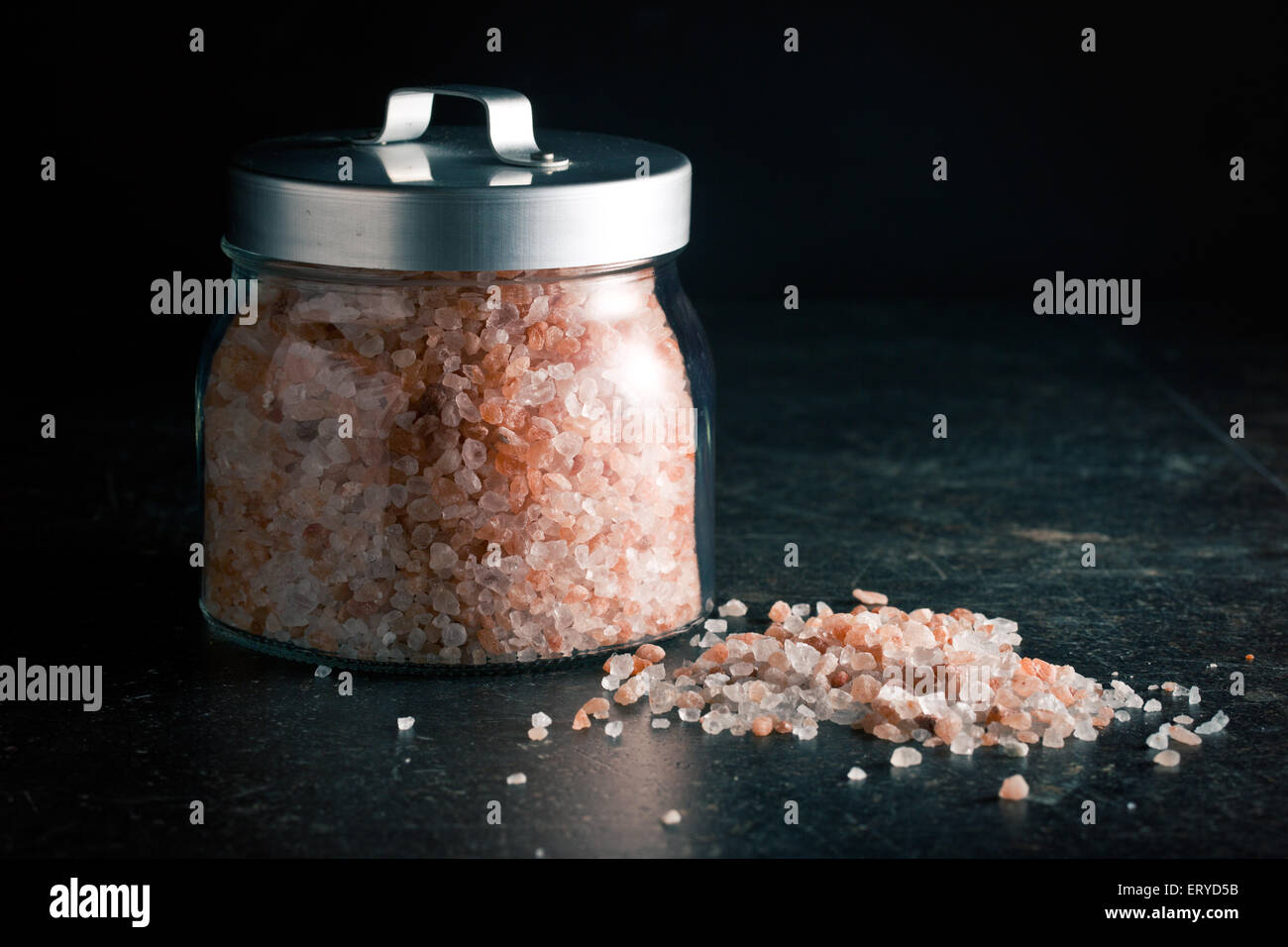 Himalayan salt in jar on kitchen table - Stock Image