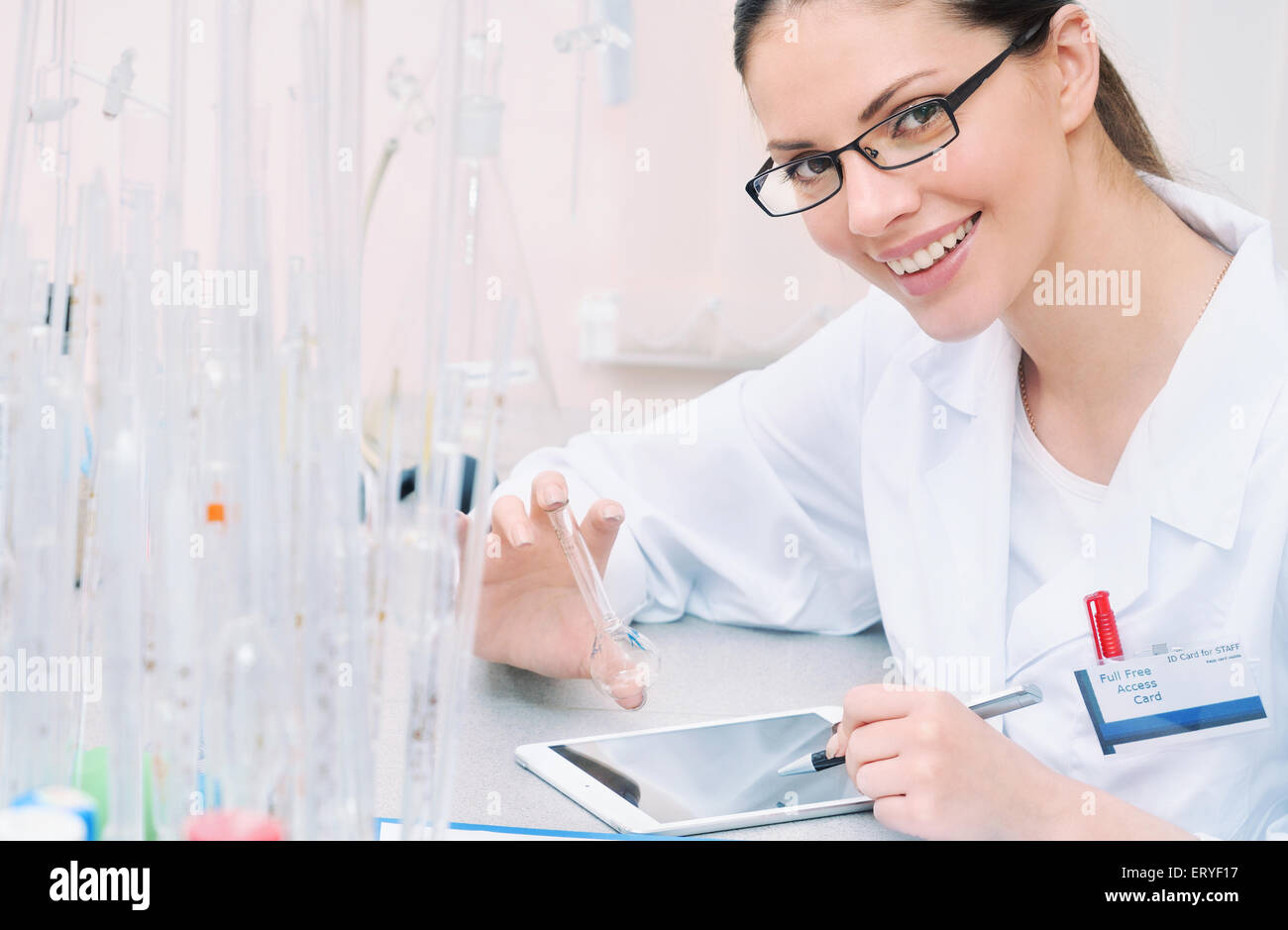 chemical laboratory scene: attractive young student scientist observing liquid measures, medicine concept - Stock Image