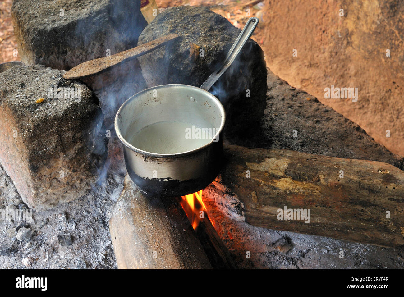 Water boiling in teapot on firewood ; Tamdi Surla ; Goa ; India - Stock Image
