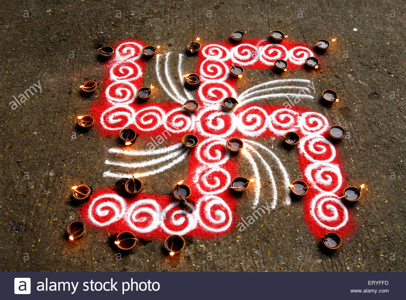 Rangoli floor design with swastik and lighted clay lamps during diwali deepawali festival 2009 Stock Photo