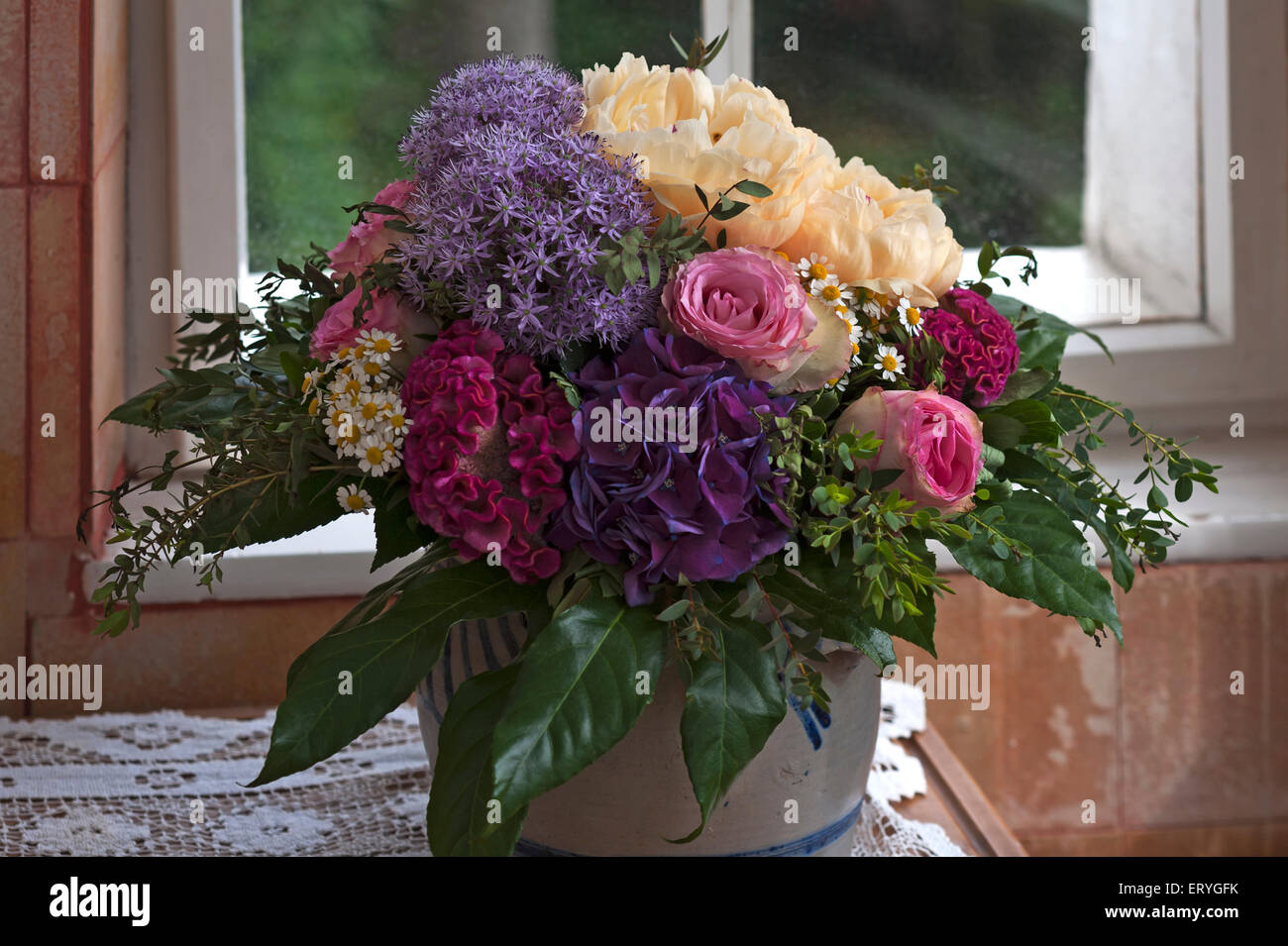 Colourful spring bouquet in front of window - Stock Image