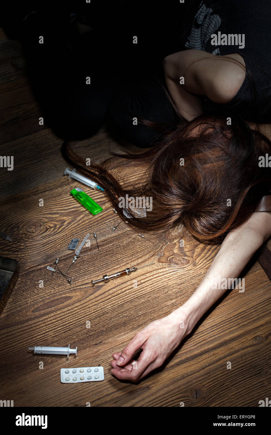 Young woman poses as an unconscious drug addict, concept photo. - Stock Image