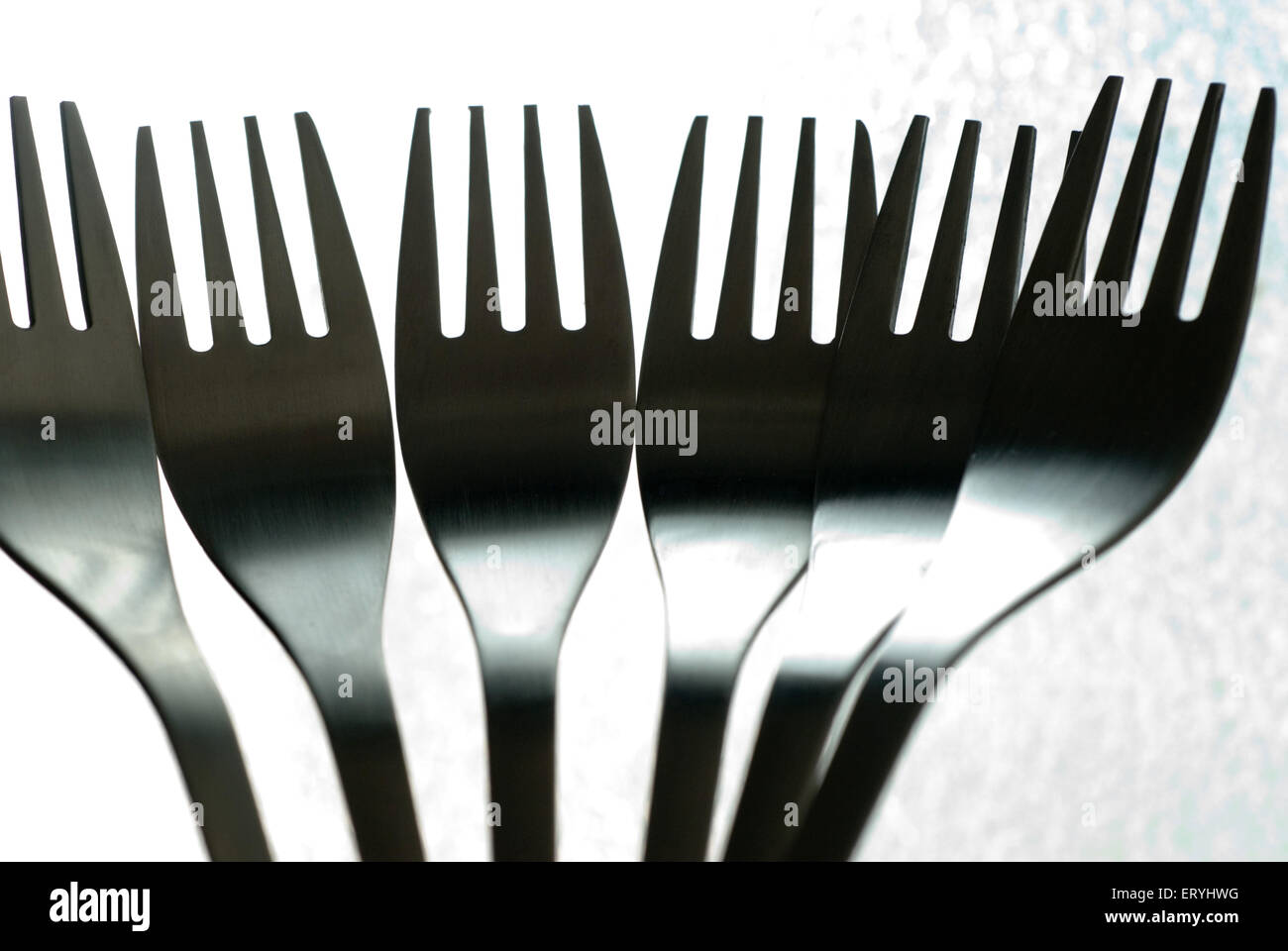 Stainless steel kitchen utensil forks on bright background - Stock Image