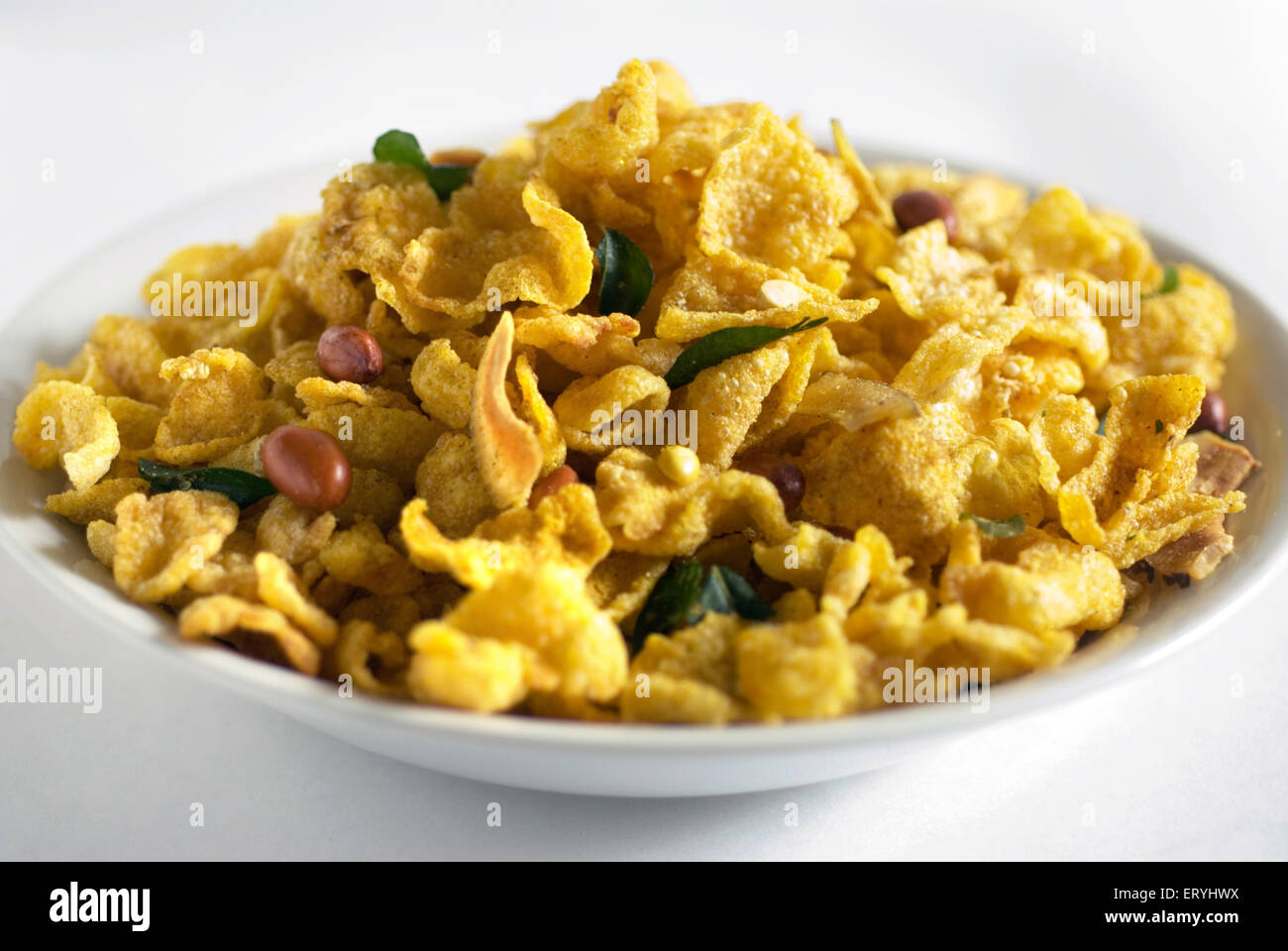 Snacks ; corn flakes fried yellow maka chivda served in dish on white background - Stock Image