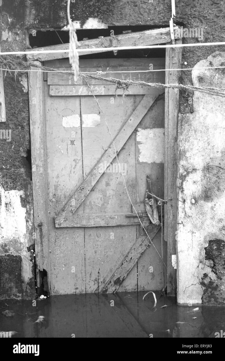 Submerged door in monsoon water in malvani slum ; Malad ; Bombay Mumbai ; Maharashtra ; India - Stock Image