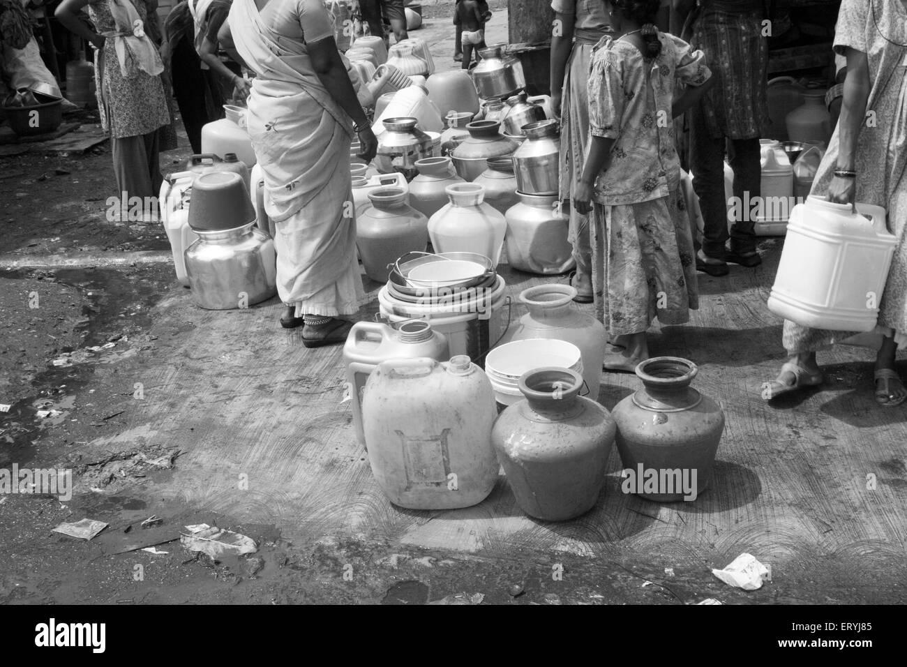 Queue for water in slum ; Mahim ; Bombay Mumbai ; Maharashtra ; India - Stock Image