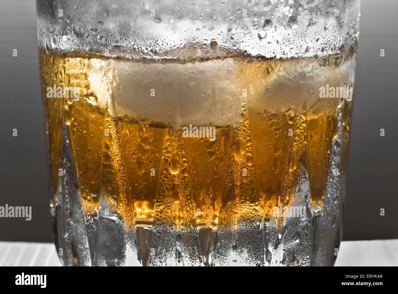 Drinks ; shimmering glass of whisky with ice - Stock Image