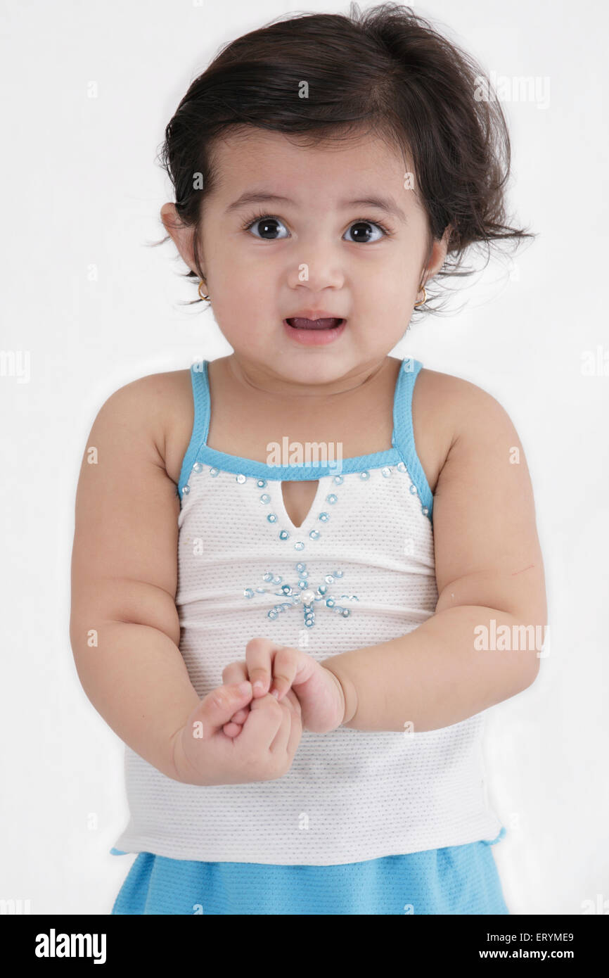Fifteen month old baby girl standing both hands joined together MR#743S - Stock Image