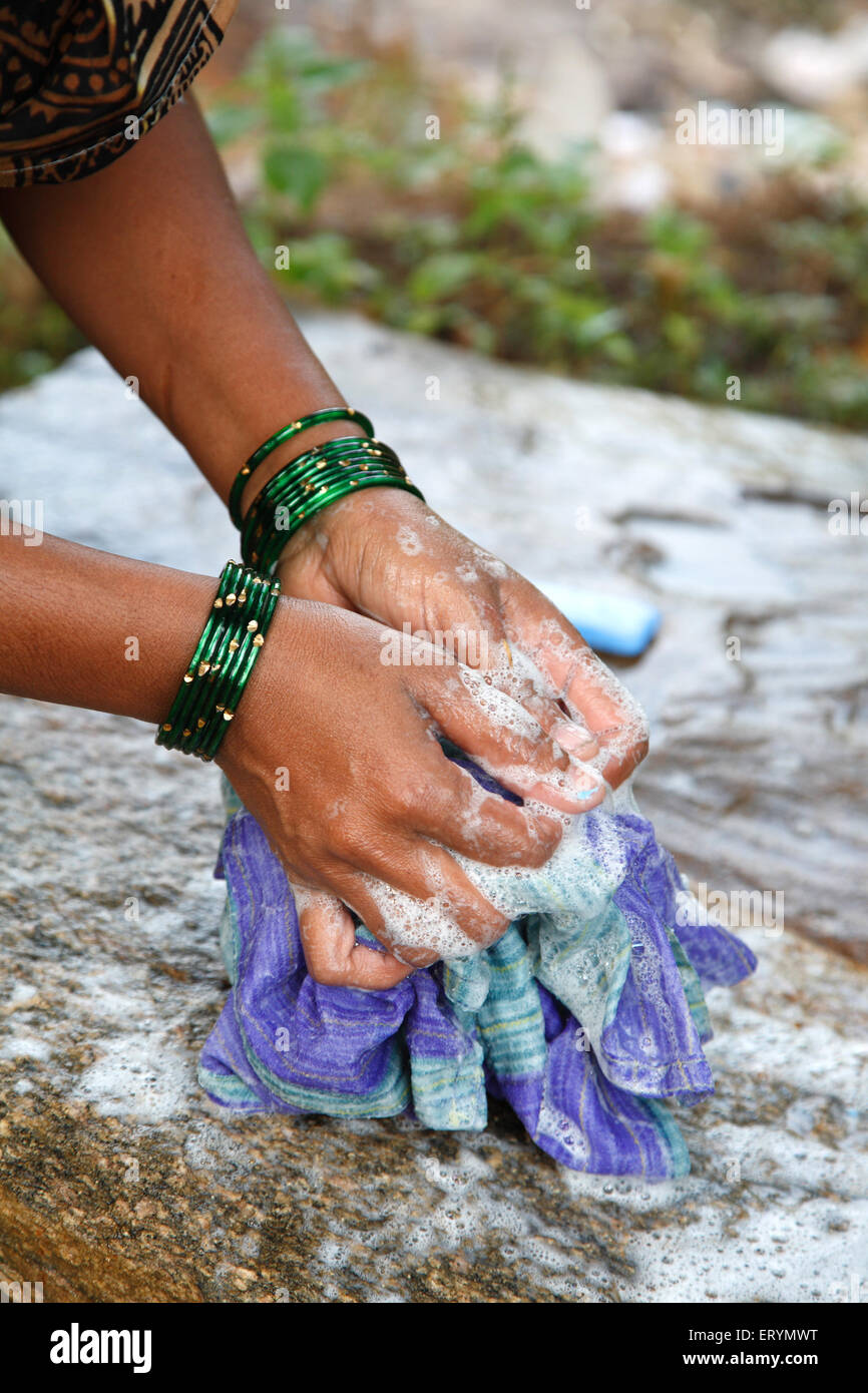 Lady washing cloths with soap rubbing on stone - Stock Image