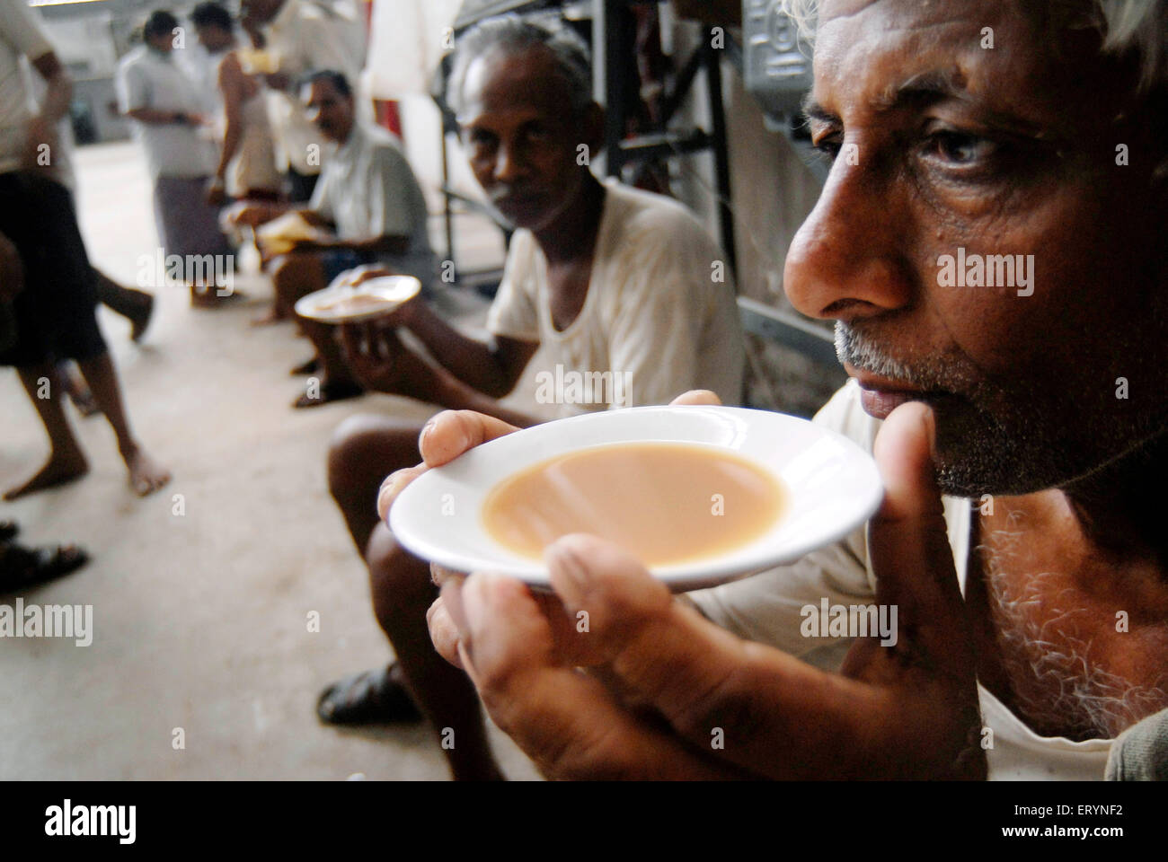 Textile mill worker sip tea during break in a textile mill in Bombay now Mumbai ; Maharashtra ; India NO MR - Stock Image