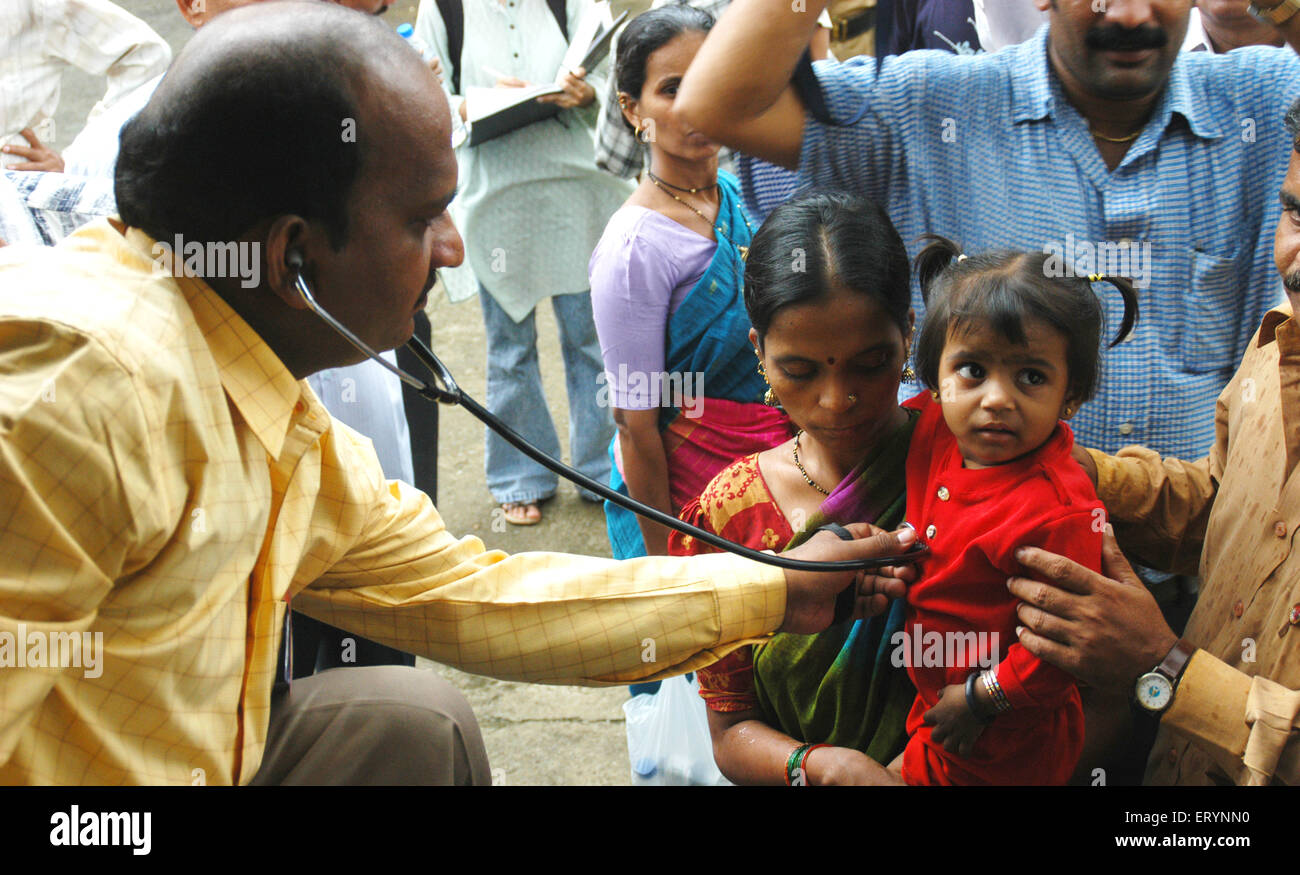 A doctor examines a child in medical camp for 26 July 2005 flood affected residents ; fears of epidemic ; Bombay - Stock Image
