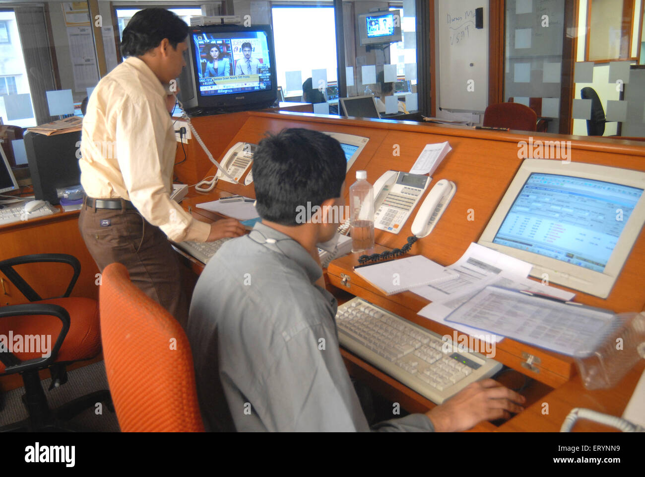 Stock brokers interact with clients to purchase shares online in a stock broking firm in Bombay Mumbai ; Maharashtra - Stock Image