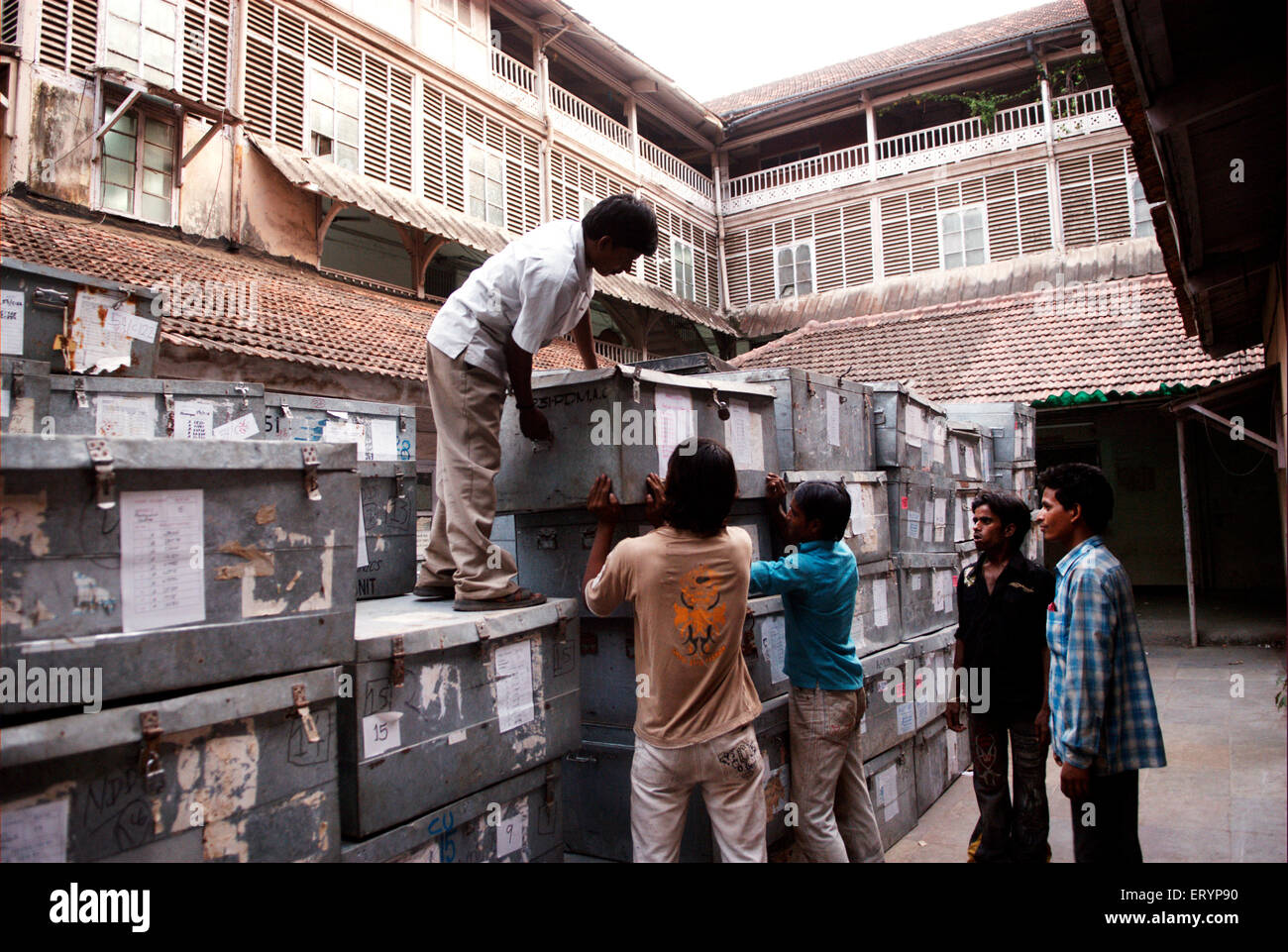 Helper boys arrange huge metal trunks containing Electronic Voting Machine EVM kept at collector office Bombay - Stock Image