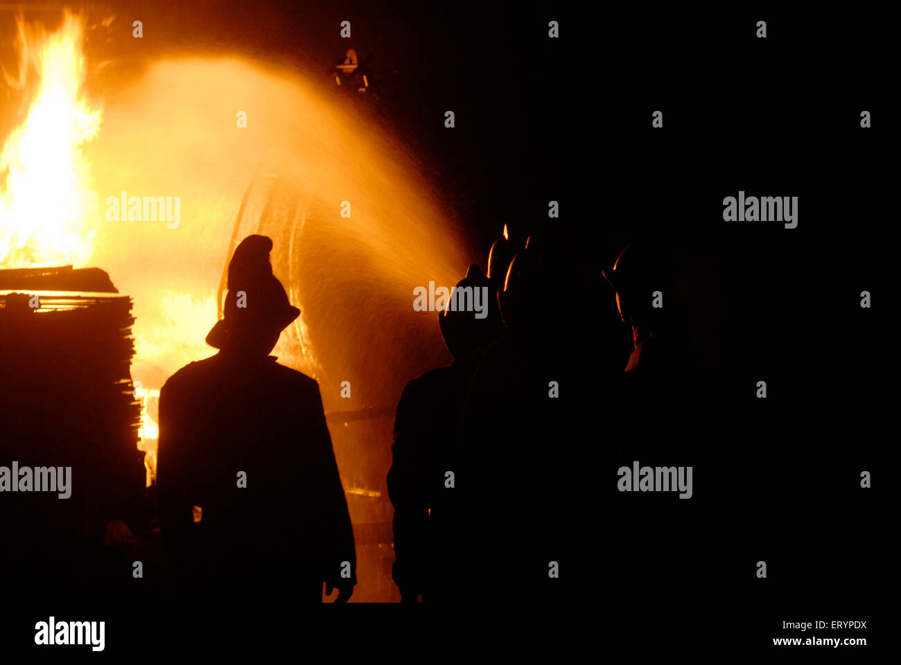 Fire brigade personnel cool fire broke out in LPG tanker with water shots at Kurla ; Bombay Mumbai ; Maharashtra - Stock Image